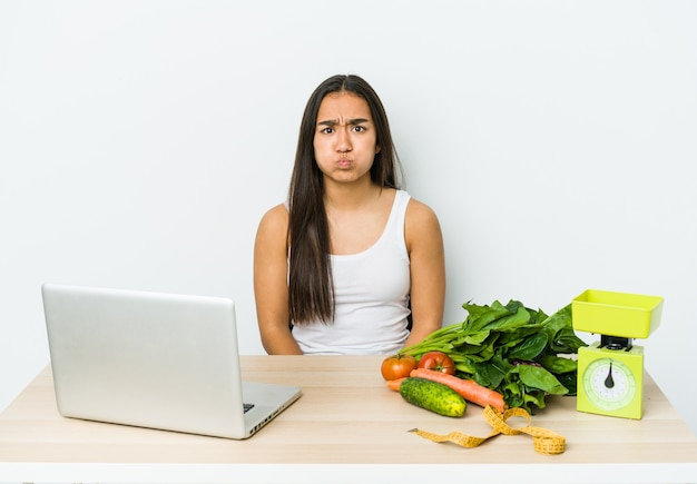 Young dietician asian woman isolated on white wall blows cheeks, has tired expression. facial expression concept.