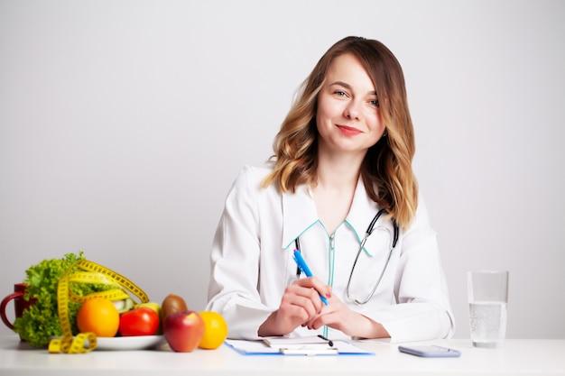 Молодой врач-диетолог в кабинете за столом со свежими овощами и фруктами работает над планом диеты