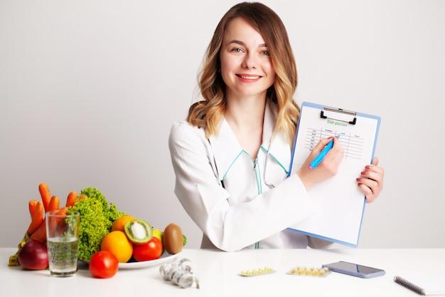 다이어트 계획에 대한 작업 신선한 야채와 과일 테이블에 상담실에서 젊은 영양사 의사