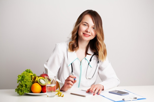 Young dietitian doctor at the consulting room at the table with fresh vegetables and fruits, working on a diet plan