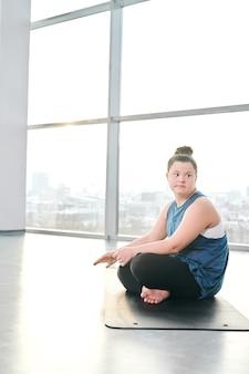 ジムでマットの上に座って、フィットネスやヨガのインストラクターを待っている間、彼女の足を交差させるアクティブウェアの若い女性を無効にします