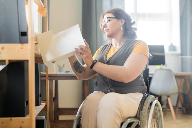 Молодая женщина-офисный работник-инвалид просматривает бумаги в одной из папок с документами на полке в поисках примера контракта