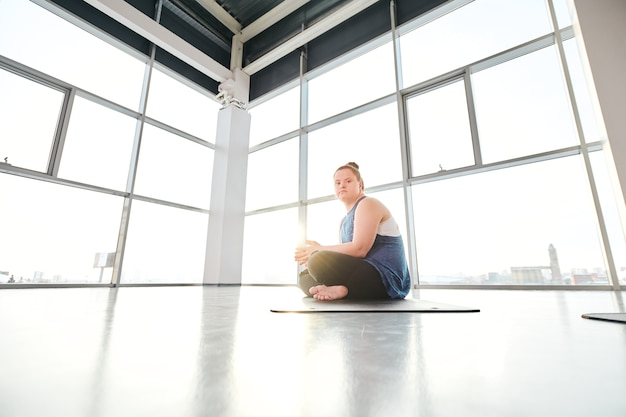 Young disable female with crossed legs doing yoga exercise on mat in gym