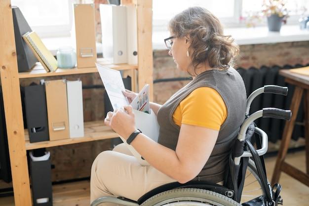 フォルダーのグループが付いている木製の棚のそばに座っている間、車椅子の若い無効なオフィスの秘書または会計士が財務書類を見て
