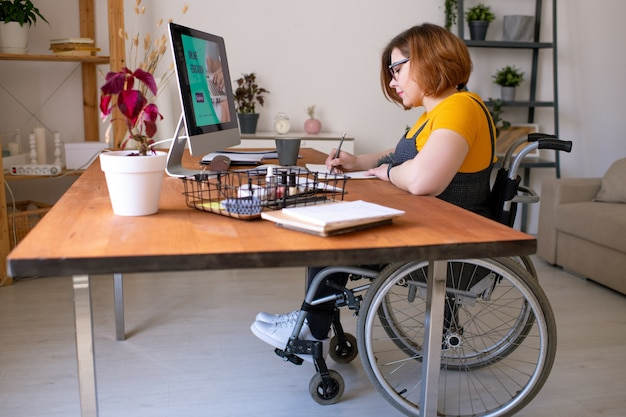 원격 수업 중 집에서 책상에 앉아있는 동안 휠체어에서 젊은 여성이 컴퓨터 모니터 앞에서 메모를 작성하지 못함