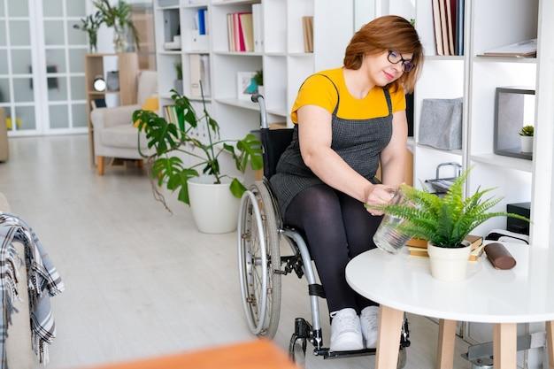 책장에 의해 작은 원형 테이블에 서있는 흰색 화분에 녹색 국내 고사리 식물을 급수하는 휠체어에 젊은 여자를 비활성화