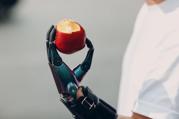 Молодой человек-инвалид держит яблоко с искусственным протезом руки в повседневной одежде