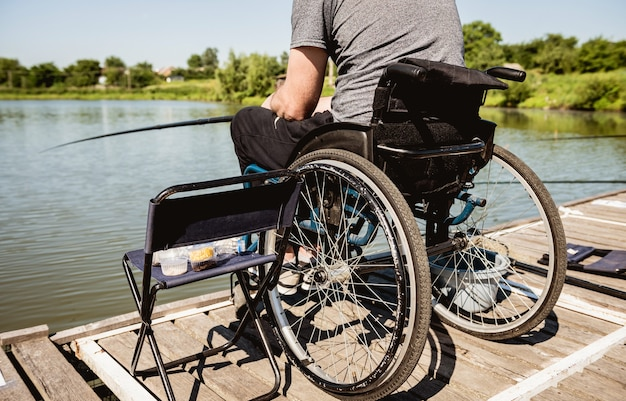 Молодой человек-инвалид в инвалидной коляске на рыбалке