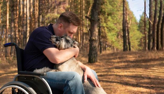 自然の中で一緒にくつろぐ魅力的な訓練された犬をなでる車椅子の若い障害者男性