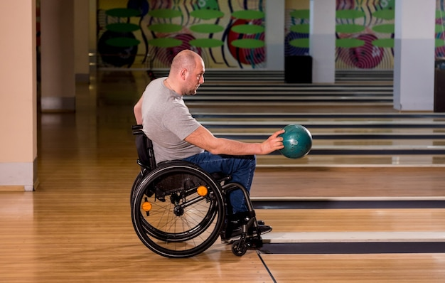 クラブでボウリングをしている車椅子の若い障害者の男性
