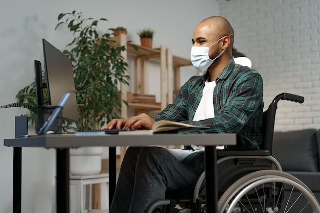 Молодой человек-инвалид в инвалидной коляске сидит за своим рабочим столом в маске для лица