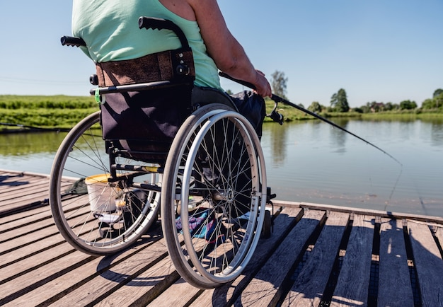 Young disabled man in a wheelchair fishing