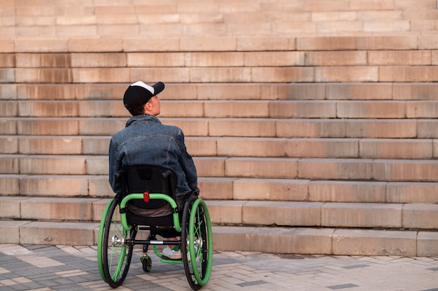 Young disabled man in wheelchair in front of stairs high quality photo
