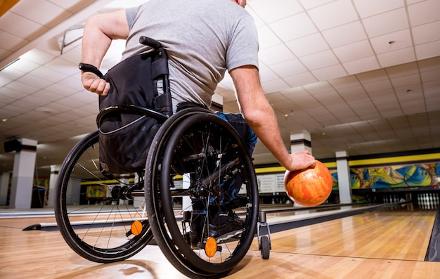 Young disabled man in wheelchair playing bowling in the club