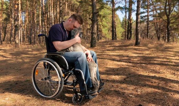 Young disabled man in a wheelchair stroking a charming trained dog relaxing together in nature