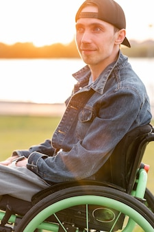 Young disabled man in wheelchair walking park high quality photo