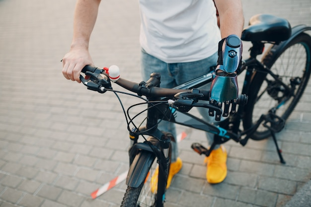 Young disabled man with artificial prosthetic hand in casual clothes going riding bike