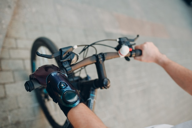 Young disabled man with artificial prosthetic hand in casual clothes riding bicycle