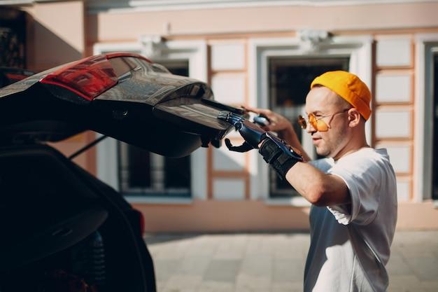 자동차 차량의 뒤쪽 트렁크를 닫는 인공 의수를 가진 젊은 장애인