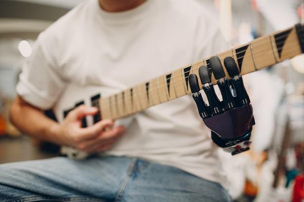 인공 의수를 가진 젊은 장애인 남자가 악기 가게에서 일렉트릭 기타를 연주한다