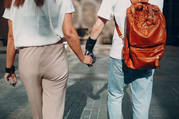 Молодой человек-инвалид с искусственным протезом руки идет и держит руку подруги женщины
