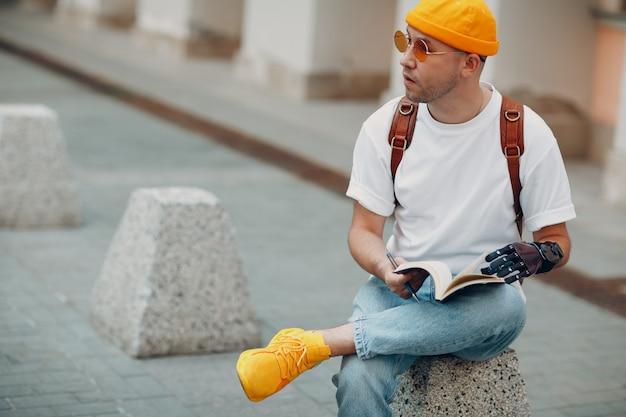 Молодой инвалид пишет в блокноте ручкой в искусственном протезе руки на улице города на открытом воздухе ...