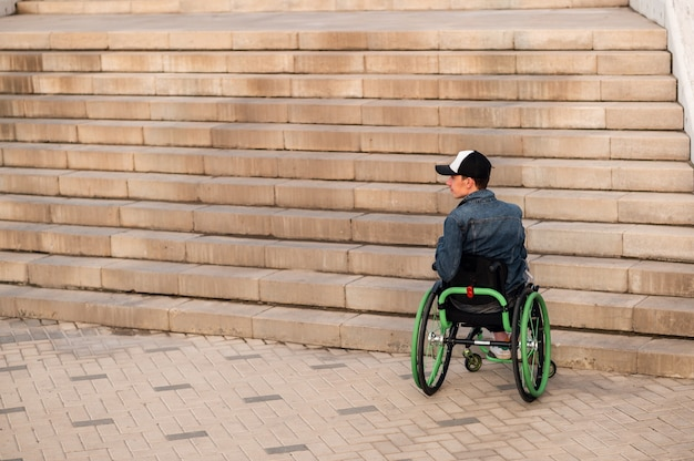 A young disabled person in a wheelchair can not enter the stairs accessible environment for the disabled high quality photo