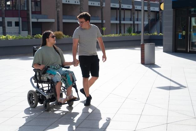 車椅子の若い障害のある女性と彼女の愛する彼氏または夫が手をつないでお互いを見ている