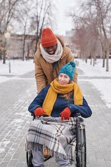 Молодая женщина-инвалид в инвалидной коляске наслаждается прогулкой на свежем воздухе с африканским мужчиной за ее спиной