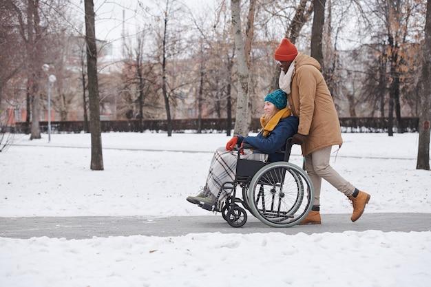 Молодая женщина-инвалид сидит в инвалидной коляске с африканским мужчиной, идущим за ней, они гуляют на открытом воздухе