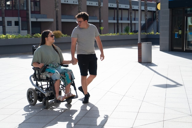 Young disabled woman in wheelchair and her loving boyfriend or husband holding hands and looking at each other