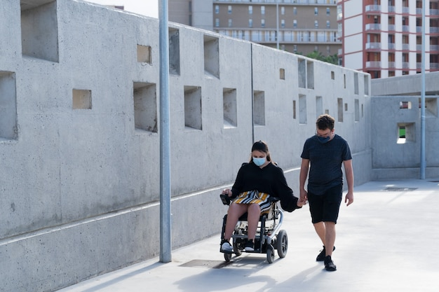 Young disabled woman in wheelchair and her loving boyfriend or husband holding hands