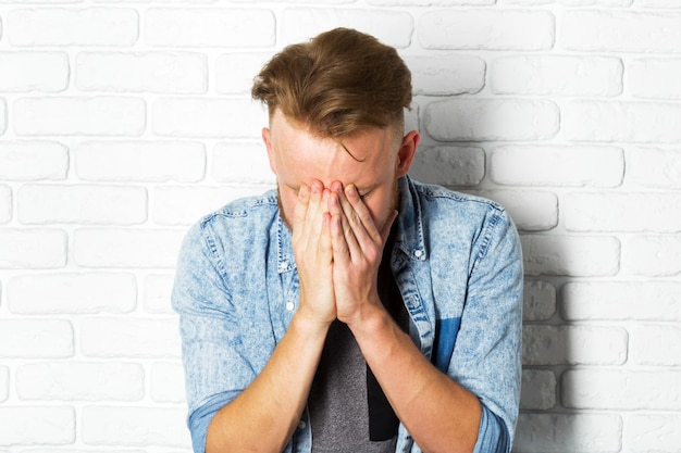 Young disappointed man is covering his face