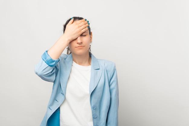 若い失望した女性は顔の手のひらのジェスチャーをしています。