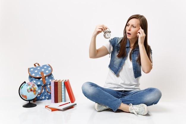 Young dismayed puzzled woman student holding alarm clock keeping hand on temple sitting near globe, backpack, school books isolated