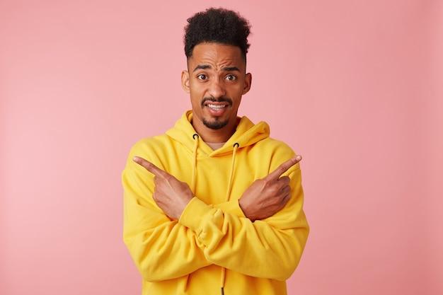 Giovane ragazzo afroamericano dispiaciuto in felpa con cappuccio gialla, braccia incrociate punta le dita in direzioni diverse senza capire dove andare, guardando.