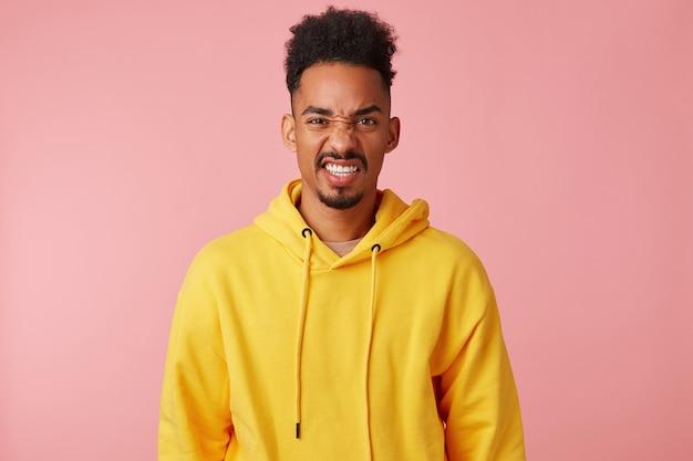 Giovane ragazzo afroamericano dispiaciuto in felpa con cappuccio gialla, accigliato e guardando con disgusto, in piedi.