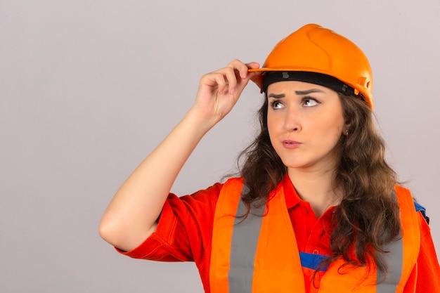建設ユニフォームと安全ヘルメット探していると分離の白い背景の上に彼女のヘルメットに触れることを考えて若い不満ビルダー女性