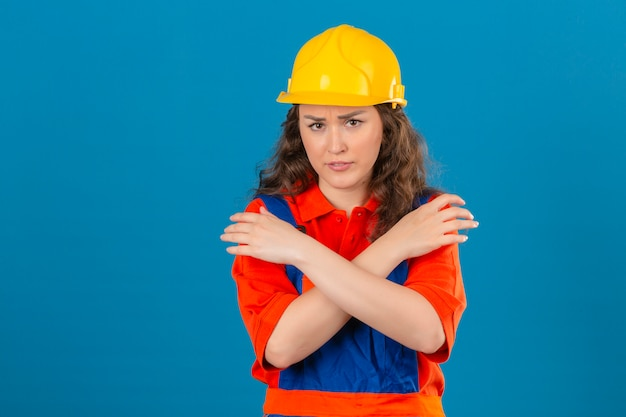 分離の青い背景上の胸に組んだ腕で制服と安全ヘルメットの立っている若い不満ビルダー女性
