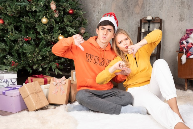 Young displeased couple embracing and giving thumbs down near the christmas tree.