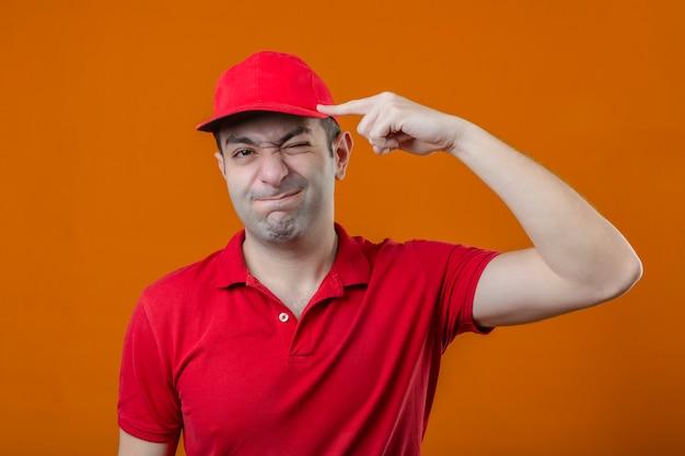 Молодой недовольный курьер в красной рубашке поло и кепке в напряжении жестикулирует пальцем у виска, не зная, что делать дальше на изолированном оранжевом фоне