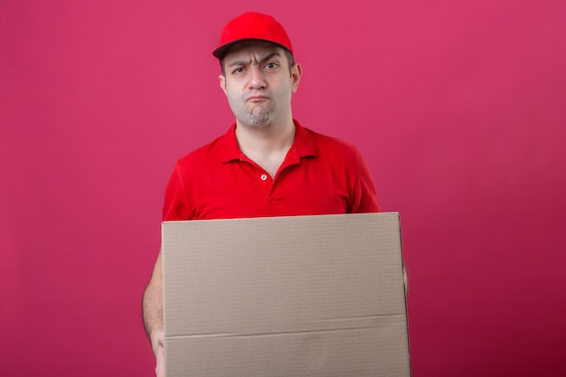 Young displeased delivery man in red polo shirt and cap holding cardboard box looking at camera with angry expression over isolated pink background