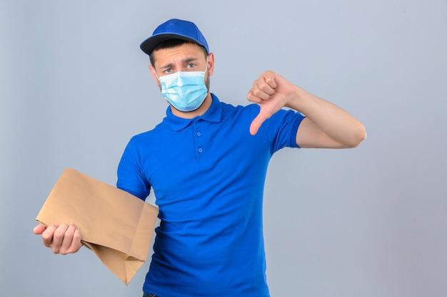 Giovane uomo dispiaciuto di consegna che indossa la polo blu e il cappuccio nella mascherina medica protettiva che sta con il pacchetto di carta che mostra il pollice giù sopra fondo bianco isolato