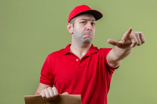 고립 된 녹색 배경 위에 손가락으로 카메라를 가리키는 종이 패키지를 들고 빨간색 유니폼을 입고 젊은 불쾌 배달 남자