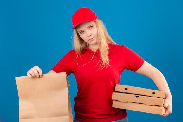 Молодая недовольная женщина-доставщик в красной рубашке поло и кепке, стоящая с бумажным пакетом и коробками для пиццы, глядя в камеру на изолированном синем фоне