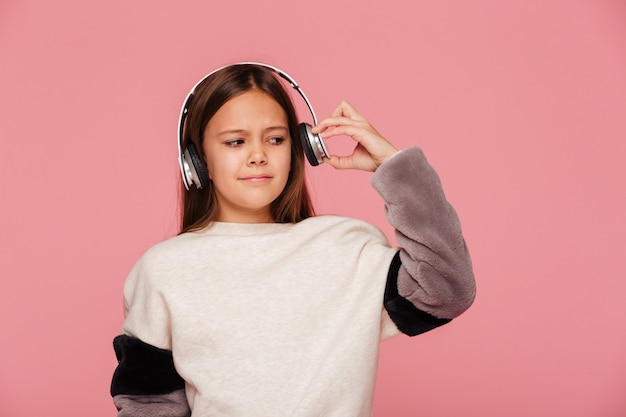 Young displeased girl push her headphones because of loudness