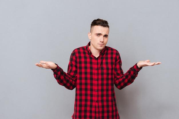 Молодой человек недоволен в рубашке, делая недовольный жест