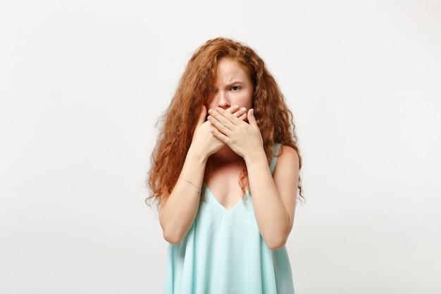 スタジオで白い背景に分離されたポーズをとってカジュアルな薄着の若い不機嫌な赤毛の女性の女の子。人々の誠実な感情のライフスタイルの概念。コピースペースをモックアップします。手で口を覆う。