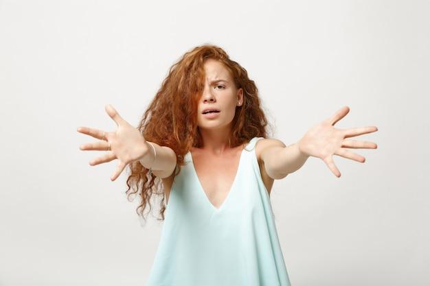 白い壁の背景に分離されたポーズでカジュアルな明るい服を着た若い不機嫌な赤毛の女性の女の子。人々の誠実な感情のライフスタイルの概念。コピースペースをモックアップします。伸ばした手で立っています。