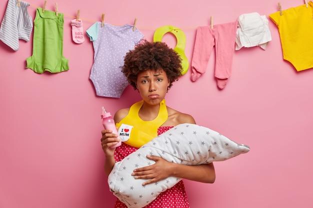 피곤한 젊은 엄마는 아기를 담요에 싸서 안고 젖병을 들고 목에 턱받이를 끼고 신생아에게 먹이를 주려고 집에 대해 많은 일을하고있다. 엄마 간호 작은 딸. 한 부모 가족